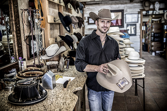 Jeff Biggar holding a hat in his hat shop