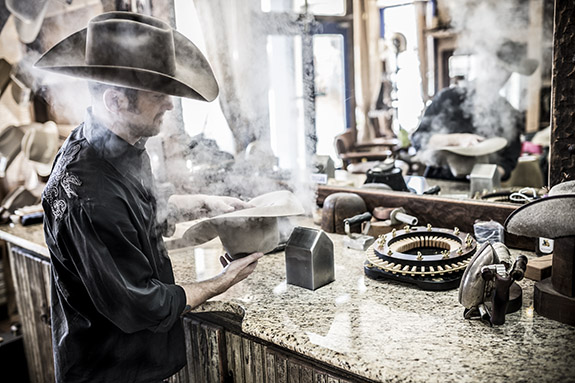 Jeff Biggar steaming and shapping a hat in his hat shop
